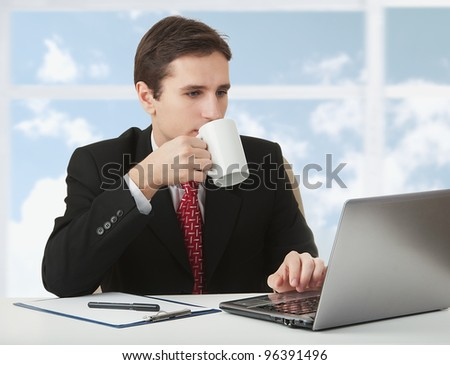 young successful business man working behind the notebook, sitting at a desk with a cup of coffee on the background of a window to the sky and clouds - stock photo
