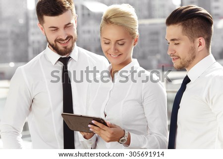 Young successful business woman surrounded by two beautiful business men - stock photo