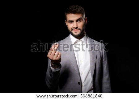 Young successful businessman asking for money over black background.
