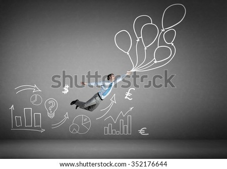 Young successful businessman flying on bunch of drawn balloons - stock photo