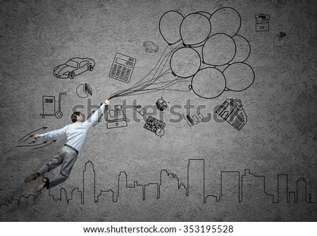 Young successful businessman flying on bunch of drawn balloons on concrete background - stock photo