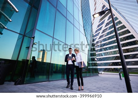 Young successful businessman in luxury suit is reading monthly report on portable digital tablet, while his female secretary with mobile phone and folder documents in hand is commenting her work - stock photo