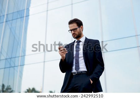 Young successful businessman pensive typing on his cellphone - stock photo
