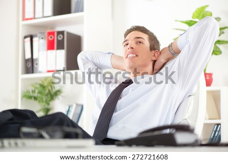 Young successful businessman relaxing in the office with hands behind  head and daydreaming. In the background you can see the shelves with binders.
