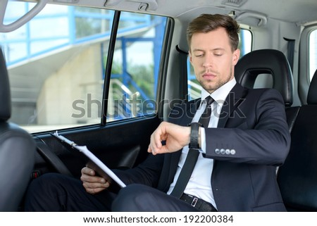 Young successful businessman riding in the car