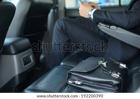Young successful businessman riding in the car - stock photo