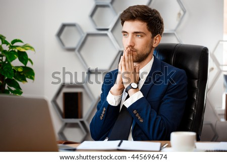 Young successful businessman sitting at workplace, office background. - stock photo
