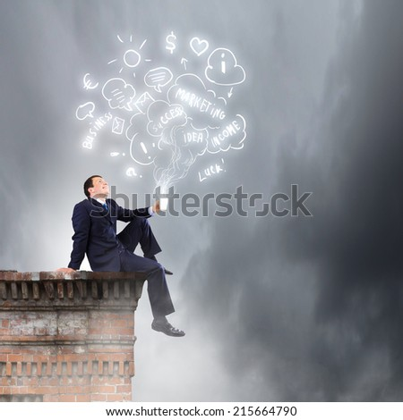Young successful businessman sitting on top of building