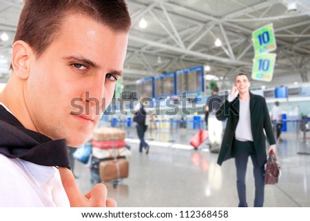 Young successful businessman smiling and looking at camera in a modern airport - stock photo