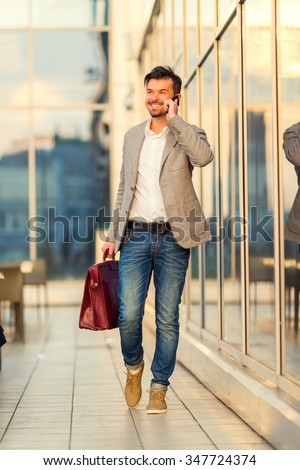 Young successful businessman talking on the phone in the background office center - stock photo