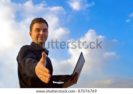 Young successful businessman working on laptop. It's his internet business, through wireless technology - stock photo