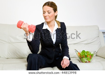 Young successful businesswoman with dumbbells and a bowl of green salad - stock photo