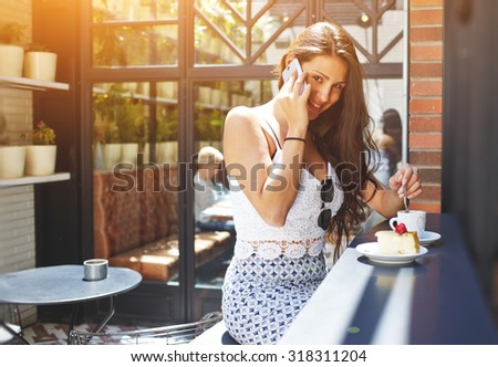 Young successful businesswoman with gorgeous smile talk on smart phone during her work break in cafe, attractive female laughing at cell phone conversation while breakfast in modern coffee shop, flare - stock photo