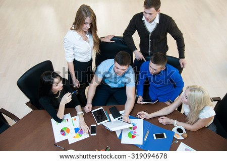 Young successful entrepreneurs at a business meeting. Business discussion. Top view - stock photo