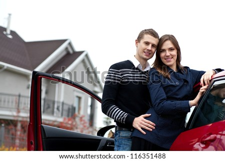 young successful family near the car against his house - stock photo