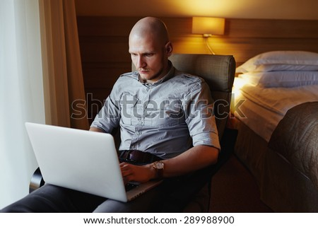 Young successful handsome man working with computer in a hotel room. Businessman traveling with work. - stock photo
