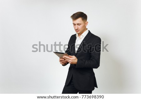 Young successful handsome rich business man in black suit working on modern tablet isolated on white background for advertising. Concept of money, achievement, career and wealth in 25-30 years