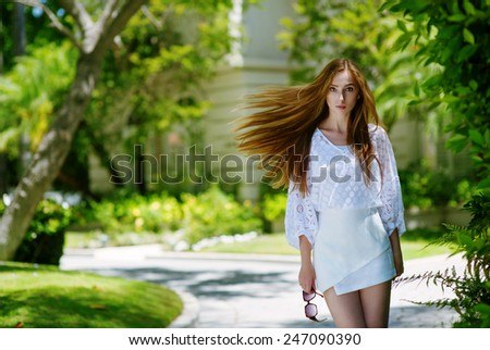 Young successful lady leaving expensive country house - stock photo