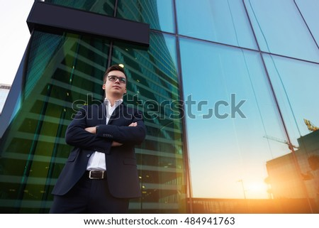 Young successful man entrepreneur dressed in suit is waiting international partners, while is standing outside his company near copy space for your advertising text message or promotional content