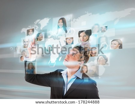 Young successful man looking at worldmap with profile photos of his colleagues and touching virtual screen. International communication concept.