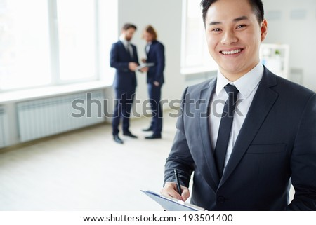 Young successful manager looking at camera while his colleagues talking on the background  - stock photo