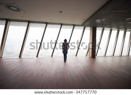 young successful startup business woman in penthouse,  modern bright duplex office apartment interior  with big windows - stock photo