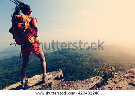 young successful woman hiker enjoy the view on mountain peak