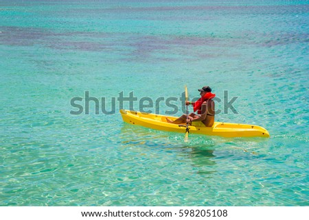 Young sun burnt man in a yellow kayak at the Caribbean sea turquoise water
