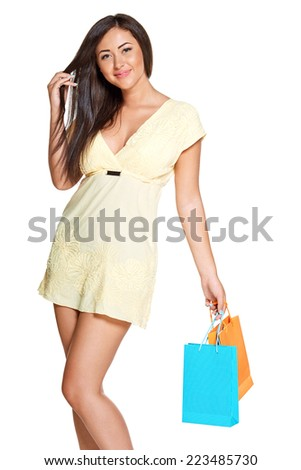 young sun-tanned woman  dressed in a lite summer yellow dress  holding colorful paper bags and smiling and looking in the camera, isolated on white background - stock photo