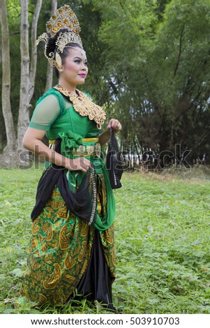 Young Sundanese dancer in full make-up and costume dancing in the forest.