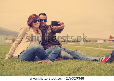 Young sunglasses couple at city park taking self portrait