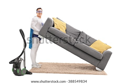 Young superhero lifting a sofa with a vacuum cleaner beside him isolated on white background - stock photo