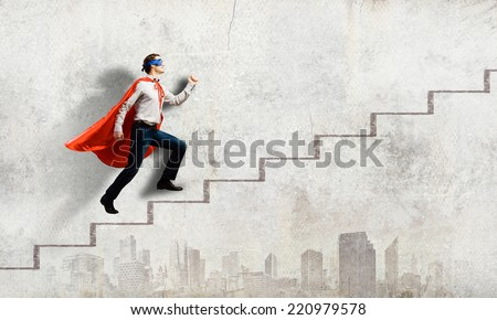 Young superman walking up the stair case - stock photo