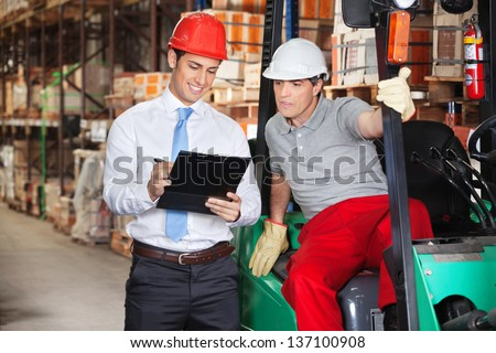 Young supervisor showing clipboard to foreman at warehouse - stock photo