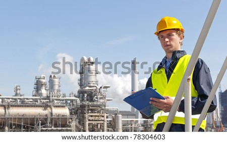 Young supervisor with a note board and pen in his hands, wearing a hard hat and safety vest in front of a petrochemical plant and refinery - stock photo