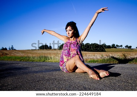 Young supple dancer sits on a french country road. She raises gracefully her arms. - stock photo