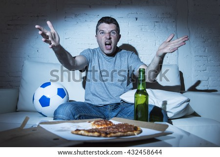 young supporter man watching football game on television sitting at home couch with ball beer and pizza in stress dejected and disappointed for failure shouting and complaining - stock photo
