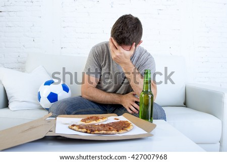 young supporter man with ball and pizza and beer bottle watching football game on television sitting at home couch in stress dejected and disappointed for failure or defeat  - stock photo