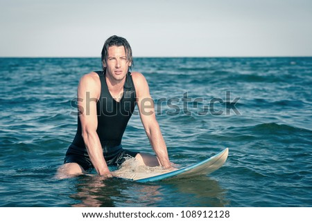 Young surf man relaxing in the water with a surfboard.