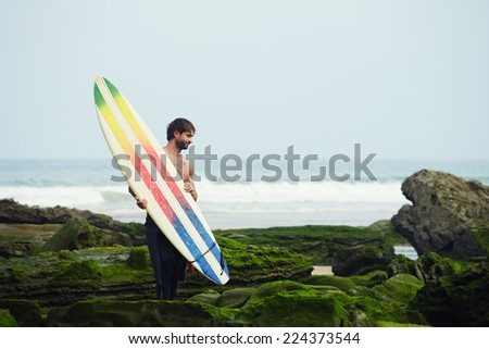 Young surfer carrying surfboard standing on moss rocks with ocean waves on background - stock photo