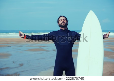 Young surfer feeling so happy, attractive surfer enjoying perfect sunny day standing on the beach and holding with one hand his surfboard, feeling good and happy with healthy lifestyle, filtered image - stock photo