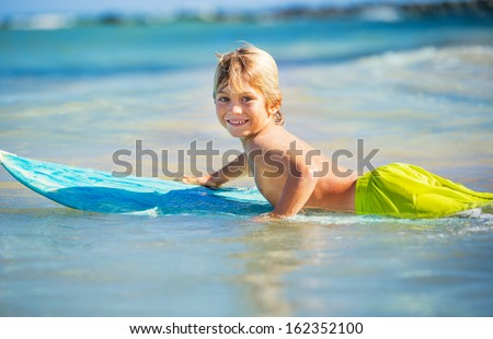 Young surfer, happy young boy in the ocean on surfboard - stock photo