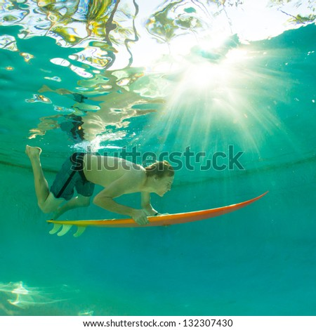 Young surfer paddling through the ocean - stock photo