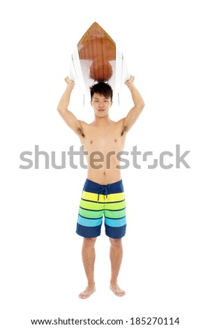 young surfer put surfboard on the head - stock photo