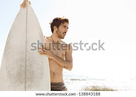 Young surfer sports man standing on a beach while wearing a neoprene rubber surfing suit during a sunny day, being thoughtful and holding a surfing board upright. - stock photo