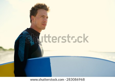 Young surfer standing on a beach at sunset backlit by the glow from the sun holding his surfboard under his arm looking seawards with a serious expression - stock photo