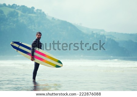 Young surfer standing on ocean beach shore, handsome brunette surfer holding his board stand on the beach waiting waves, surfer man with surfing board standing against ocean  - stock photo