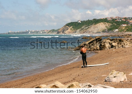 Young surfer taking his wetsuit off, Guethary beach, France. Guethary is located between Bidart and Saint Jean de Luz.  - stock photo