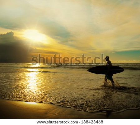 Young surfer with board on the beach - stock photo