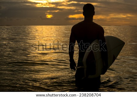 young surfer with muscular body looking for a wave for surfing against the beautiful colorful sunset Mauritius, Indian Ocean - stock photo